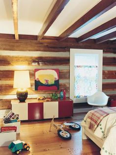Wood ceiling beams, eames rocker, red and white console, custom window shade, personal artwork.
