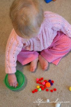Fitting Poms in Container 21 Activities for One Year Olds - Baby Play - Wildflower Ramblings