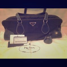 "PRADA authentic handbag black doctor bag Black Prada signature soft nylon with white stitching. Interior is lined with Prada monogram black fabric. 1 interior zip pocket.  Hard leather with 4 metal feet on bottom shape and protect the bag. Zip top closure. Lock and security key included.  Zip handle is missing but can easily be fixed (shown in pic) Made in Italy. 14""length, 7""height, 3""depth with 9"" drop double leather strap. This is from a non Smoking home. Prada Bags"