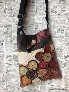 This listing is for a crossbody hobo style bag. It is designed using warm earth tones with touches of deep red. The two scrappy flower designs hand-stitched to the front help to make this one a nice statement piece that is perfect for both the young and the young at heart:) NOTABLE DETAILS: Repurposed belts work in tandem to create an adjustable strap that is comfortable to wear across the body, keeping your hands free, or simply wear it over the shoulder. The inside has a divided slider…