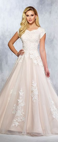 Tulle and Belgium lace full A-line gown with lace accented cap sleeves, soft sweetheart neckline, back crystal buttons, lace appliques cascade down skirt and onto chapel length train.