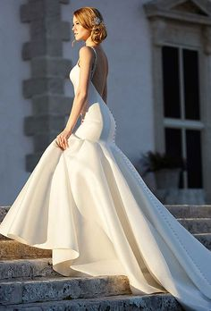 Brides: Martina Liana. See more details from Martina LianaAn impressive 600-inch hemline, fabric -covered buttons and Swarovski crystal straps complete the dramatic look of this fit-and-flare bridal gown.