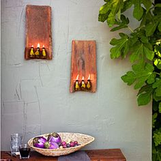 Outdoor Sconce from salvaged, clay roof tiles. Using electrical wire, attached small lipped glass bottles, which can be found at a craft store, to the tiles. Then insert lamp wicks (from the store's candlemaking section) and fill the bottles with olive oil, though lamp oil would work too. Just let the wick soak up the oil before you try to light it