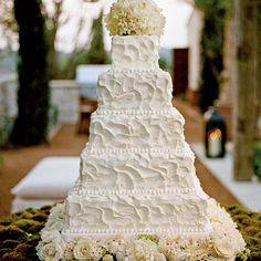 Romantic White Square Wedding Cake | The five-tiered wedding cake was decorated with white flowers and displayed on a bed of moss.