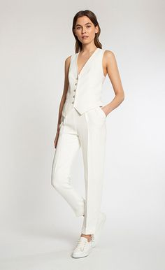 Crossback waistcoat paired with crepe high-waisted trousers. Outfit by Temperley London.