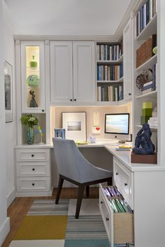 Contemporary home office painted white with lighting under shelves/cabinets