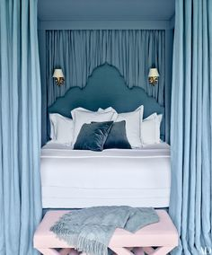 A luxe master bedroom with a canopy bed draped in blue linen and a light pink ottoman | archdigest.com
