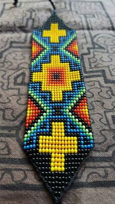 These sacred bead work bracelets are handmade by women from an indigenous cooperative from the Kamentsá tribe of the Sibundoy valley in southern Colombia. Each design is inspired by the visions received during traditional ceremonies. Loom Beading, Reggae, Perler Beads, Drink Sleeves, Friendship Bracelets, Patches, Etsy, Unique Jewelry, Handmade Gifts