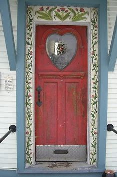 Sweet heart shaped window, distressed paint and beautiful painted flowers make this door so welcoming, there must be cookies in the oven! The pink and blue color scheme is so charming ... knock, knock?