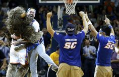 Cameron Rodriguez, second from left, celebrates with Thunder mascot Rumble, left, after hitting a half court shot to win $20,000 during a time out of an NBA basketball game between the Oklahoma City Thunder and the Denver Nuggets in Oklahoma City, Monday, Nov. 18, 2013. (AP Photo/Sue Ogrocki)