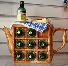 Handcrafted teapot in the shape of a wine rack with 8 bottles. The ninth bottle with its chateau teapottery 1993 tea noir label is standing on the top of the checked table cloth laid ready for lunch with cheese a tomato & a loaf of bread (Swineside Ceramics Collection)