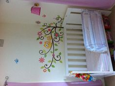 Baby girls bedroom, with wall stickers with owls and trees