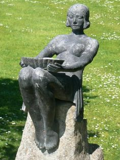 """A vintage lead fountain modelled as a girl in Art Deco styled attire holding a bowl on her lap and seated on a composition-stone rockwork base. The bowl is plumbed for use as a fountain with the water spilling into the girls lap.  Early 20th Century  28"""" high overall  £950"""