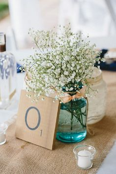 rustic wedding centerpieces bouquet of gypsophila flowers in blue mason jar with pink ribbon on natural tablecloth braun photography