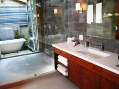 A glass partition sits in between the extra-long vanity and well-equipped walk-in shower. Exterior doors beyond the shower lead to an enclosed courtyard where a freestanding tub sits in a shallow pond with a cascading waterfall behind it.