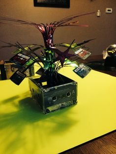 Cassete tape centerpiece . I hot glued the cassettes together and put a centerpiece from Party City in it. Perfect for an 80's party.