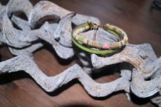 Een vrolijke dubbele armband in de kleuren groen.  Een plat Italiaans leren band gecombineerd met een vrolijke groene gestikt koord.  Normale koperen sluiting met daar aan een hangertje ster en handmade labeltje.  € 6,50