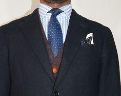 Navy sport coat, light blue gingham shirt, navy tie, light grey pants, brown sweater
