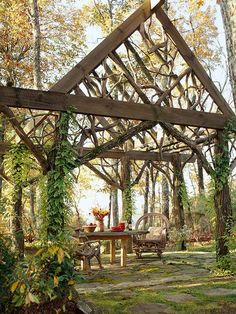 Blend into Nature - This wooden structure does a great job of blending into it's natural surroundings while still establishing the space as an outdoor room. A wooden table and chairs made out of twisted branches continue the nature-inspired look. Vines growing up the structure's supporting beams help to further conceal the piece.