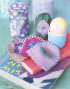 """Transform a swatch of felt into an egg warmer. Cut two rectangles, about 3 1/2"""" x 4"""", rounding top ends with scissors. Use embroidery floss to blanket-stitch pieces together. Add an iron-on appliqué, if desired."""