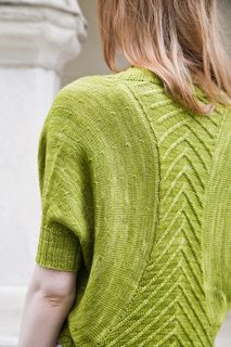 This seamless bolero-style cardigan begins with a cabled back that is worked flat back and forth with shaping. The sleeves are picked up and worked in the round with decreases, creating a cone shape. The fingering weight yarn has drape and makes this an easy-to-wear piece.