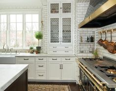 A tiled cooking alcove is filled with a black kitchen hood with brass trim placed over a brass pot rack mounted on the backsplash as well as a black French stove, La Cornue Grand Palais 180.