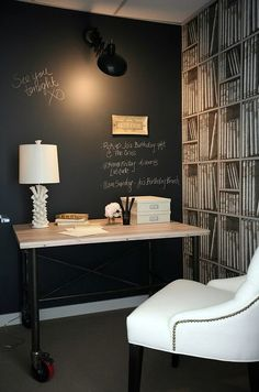 loooooove this!! // White & black sophisticated office design with black chalkboard accent wall, industrial reclaimed desk, white lamp, Restoration Hardware Martine white tufted chair with nailhead trim and faux library bookshelves wallpaper.