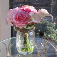 Beautiful rose and calla lily arrangement in mason jar with faux water.