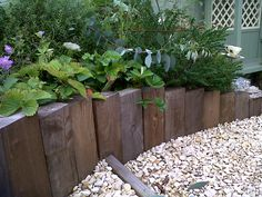 These wood half sleepers provide a good retaining edge in my garden