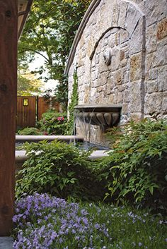 The rough-hewn stone and concrete fountain lends a feeling of maturity and grace to this landscape. By Bonick Landscaping in Dallas, TX.