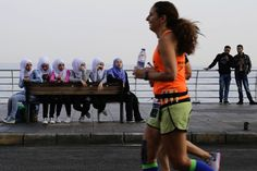 Citizens watch runners compete in the 42 kilometer (26 mile) Beirut Marathon in Beirut, Lebanon. (HASSAN AMMAR / AP)