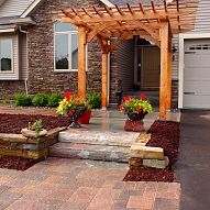 Custom cedar arbor enhances home's front entrance and paver patio provides sitting and gathering area.