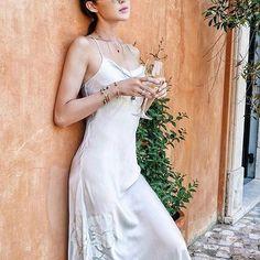 @chrisellelim reflects peacefully on vacation wearing the silky #JosieNatori Vivien gown. Get her look at natori.com! ✨ #slipdress #silk #fashion #summerstyle #romance #getaway #chrisellelim