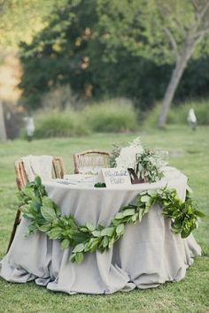 Use a natural color palette and some leafy green décor for your sweetheart table at an outdoor reception.