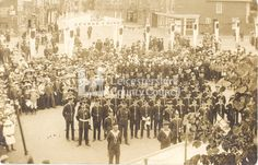This photograph shows the celebrations for the coronation of King George V on the 23rd of June 1911. It was taken by Thomas Kay from a first-floor window on the west side of the Square in Market Harborough.   The people of Harborough watch uniformed groups of men parade in the Town Square. These groups include local volunteer regiments, the fire brigade and the boy scouts. In the background is the coronation banner.