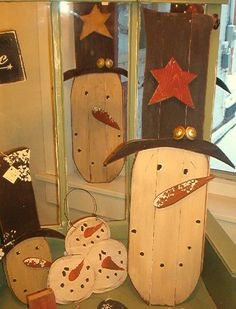 Hand crafted wood snowmen head faces.