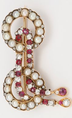 """A FABERGÉ JEWELED BROOCH, WORKMASTER EDUARD SCHRAMM, ST. PETERSBURG, 1898-1904 the brooch formed of two pearl-set rings entwined with a """"chain"""" of rubies and diamonds with drop-shaped pendants, struck with workmaster's initials, 56 standard, contained in red leather-bound fitted case width 1 3/4 in. (4.5 cm)"""