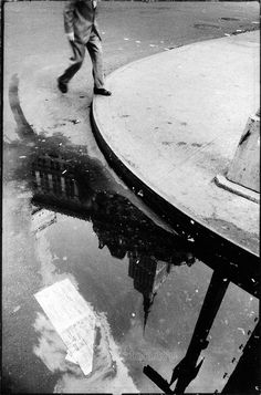 Empire State Building reflected in a puddle, NYC, 1961, from an incomplete series called '100 Views of Empire State' (after Hokusai's '100 Views of Fujiyama'). Exact number of images from this set unknown.  Photography by Larence N. Shustak.