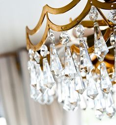 Lay a large plastic drop cloth under the hanging light fixture, spray the crystals with a streak free glass cleaner like Perfect Glass.  The excess cleaner will drip on the plastic bringing the dust & dirt with it. after, use a lint free rag to hand dry the crystals that need a touchup.