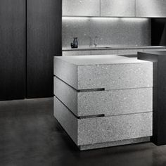 Island in grey granite with leather finish, tall cabinets in black veneer with light veins, matt finish