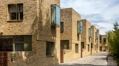 Peter Barber Architects has completed a terrace of mews houses in north London, which are arranged along a cobbled lane and feature oriel windows.