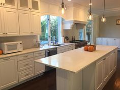 White kitchen with engineered QuartzMaster Calacatta Royal countertops & full height backsplash.  Warm wood flooring.  Kitchen by Stoneshop from Cherry Hill, NJ.