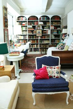 Amazing arched bookshelves (made from IKEA billy bookshelves and MDF! So easy & affordable!) and beautiful chair in the foreground with its crisp white legs and rich blue upholstery... Can I move in?