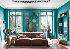 salon élégant avec une peinture turquoise, masques africaines accrochées au mur et un canapé rembourré