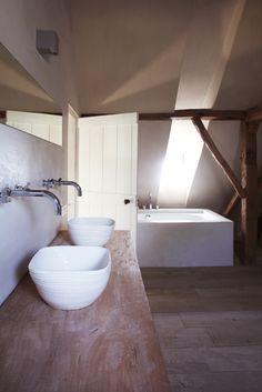 Baño rústico con lavabos de diseño sobre encimera de madera, vigas vistas, suelo de madera.