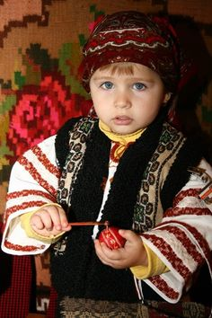 A sweet little Romanian girl plays with her toy while dressed traditionally