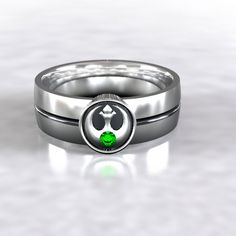 Star Wars tribute Rebel Alliance Ring! This ring comes with a Chatham lab created emerald for a nice accent stone. Also available with lab created ruby, or sapphire upon request. This 6mm wide wedding band is made from recycled silver and is handmade with a comfort fit to your size. The ring is carved from wax, then cast in the metal. From there it is finished by hand to achieve a great wearable look.  Ring Specs: ● 6mm width (7 mm at emblem) ● 1.5mm Thickness- good weight, sturdy…