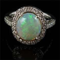This lovely 2.50ct Natural Opal ring is set in 18ct white Gold.  Surrounded by 1ct of Old Cut Diamonds  The lovely Opal is a kaleidoscope of rainbow colours Shimmering and changing colours with the light. The Opal Radiates a myriad of colours - blues, pinks, greens, turquoise and an inner orange.  The Diamonds are Circa 1900 set into a newer shank/gallery in the Victorian Style.