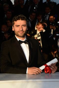 Actor Oscar Isaac poses on behalf of directors Joel and Ethan Coen after they were awarded with the Grand Prix for the film 'Inside Llewyn Davis' at the Palme D'Or Winners Photocall during the 66th Annual Cannes Film Festival at the Palais des Festivals on May 26, 2013 in Cannes, France.