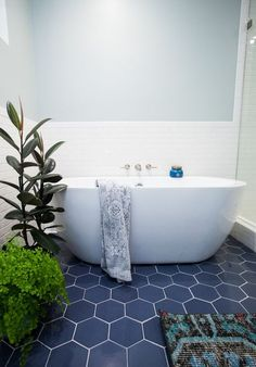 navy hex tiles with white grout give a seaside look to the bathroom